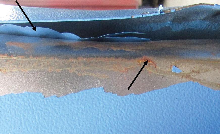 """Rys. 1. Zdeformowany element pomalowany farbą proszkową; strzałki wskazują miejsca, gdzie: powłoka """"odkleiła się"""" od blachy (jeśli w ogóle przylegała do niej) i skorodowane obszary świadczące o występowaniu wilgoci pomiędzy blachą a powłoką."""