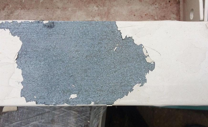 Utrata przyczepności powłoki lakierowej do ocynkowanego podłoża najprawdopodobniej w wyniku niewłaściwego oczyszczenia powierzchni przed malowaniem proszkowym.