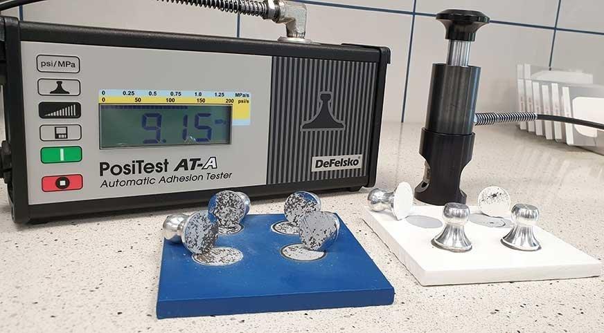 Powłoki farb na metal podczas testów ASTM D4541 w laboratorium Spektrochem.